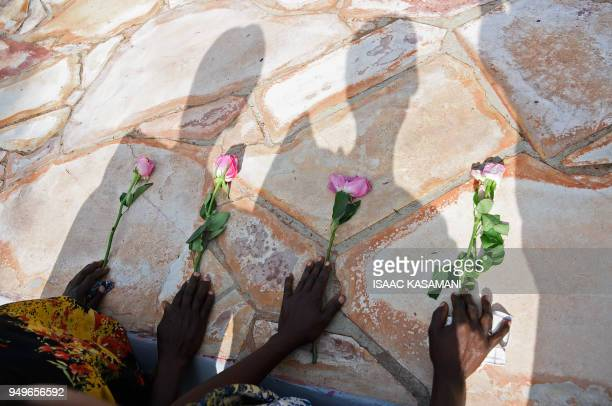 Rwandese refugees in Uganda place flowers as they pray at Kasensero Genocide Memorial site in Rakai District on April 21 2018 as they mark the 24th...