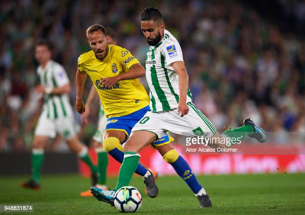 Ryad Boudebouz of Real Betis Balompie being followed by Javi Castellano of Union Deportiva Las Palmas during the La Liga match between Real Betis and...