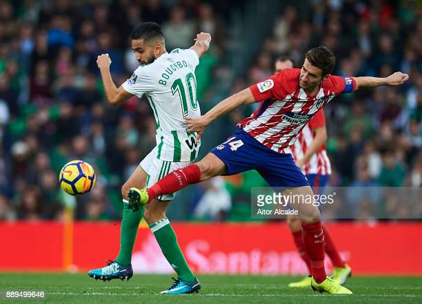 Ryad Boudebouz of Real Betis Balompie competes for the ball with Gabi Fernandez of Club Atletico de Madrid during the La Liga match between Real...