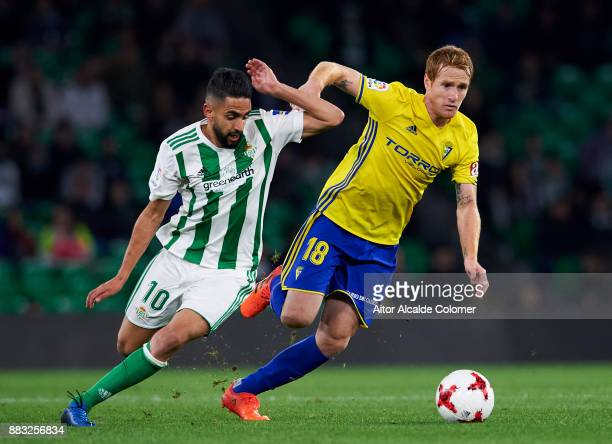 Ryad Boudebouz of Real Betis duels for the ball with Alejandro Fernandez of Cadiz during the Copa del Rey Round of 32 Second Leg match between Real...
