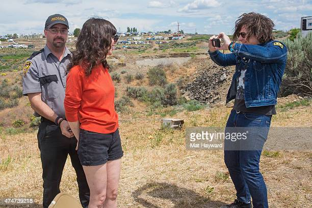 Ryan Adams takes a photo as a security guard handcuffs Natalie Prass during the Sasquatch Music Festival at The Gorge on May 25 2015 in George...