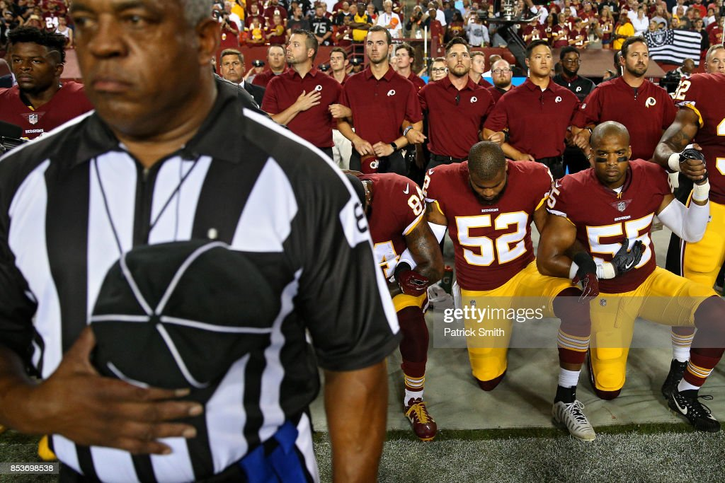 Ryan Anderson #52, Chris Carter #55 and Niles Paul #84 of the Washington Redskins lock arms as they kneel alongside standing coaching staff and teammates during the United States national anthem before playing against the Oakland Raiders at FedExField on September 24, 2017 in Landover, Maryland. U.S. President Donald Trump chastised the NFL and its players publicly on Twitter regarding those who kneel during the national anthem, so more than 200 players league wide showed their solidarity during week three of the NFL regular season by demonstrating in the form of kneeling, sitting or joining arms during the playing of the anthem.