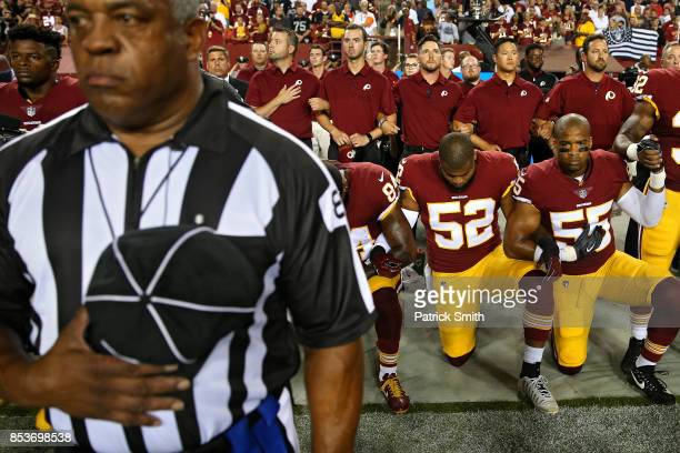 Ryan Anderson Chris Carter and Niles Paul of the Washington Redskins lock arms as they kneel alongside standing coaching staff and teammates during...