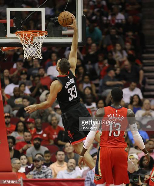 Ryan Anderson of the Houston Rockets dunks as Cheick Diallo of the New Orleans Pelicans looks on at Toyota Center on March 24 2018 in Houston Texas...