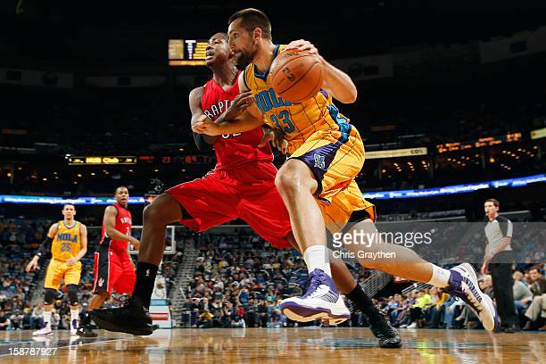 Ryan Anderson of the New Orleans Hornets drives the ball arount Ed Davis of the Toronto Raptors at New Orleans Arena on December 28 2012 in New...