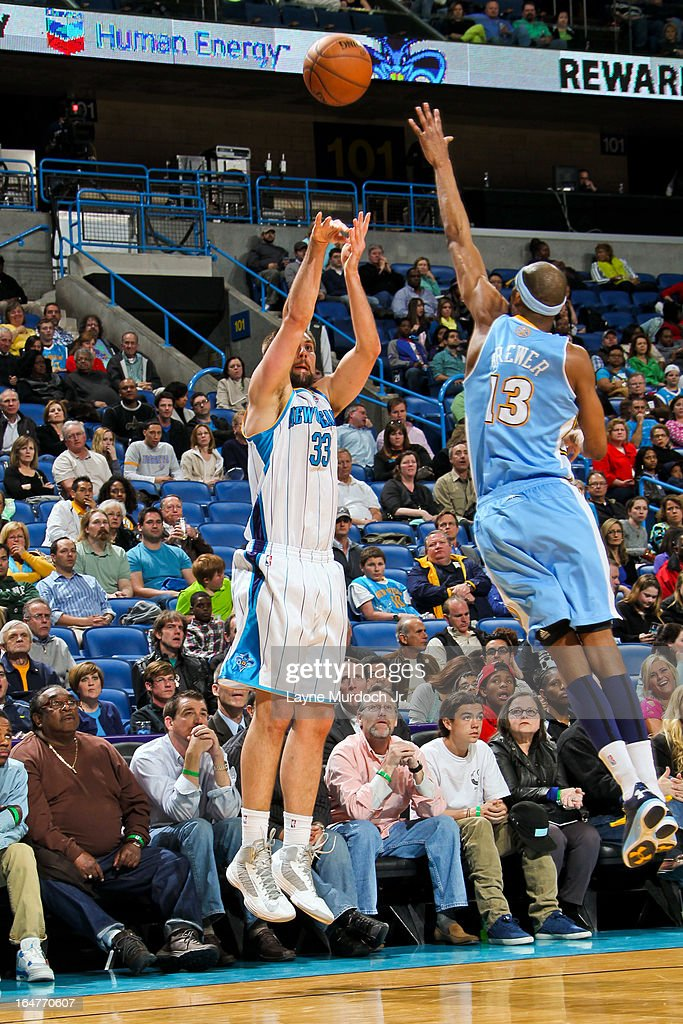 Ryan Anderson #33 of the New Orleans Hornets shoots a three-pointer against Corey Brewer #13 of the Denver Nuggets on March 25, 2013 at the New Orleans Arena in New Orleans, Louisiana.