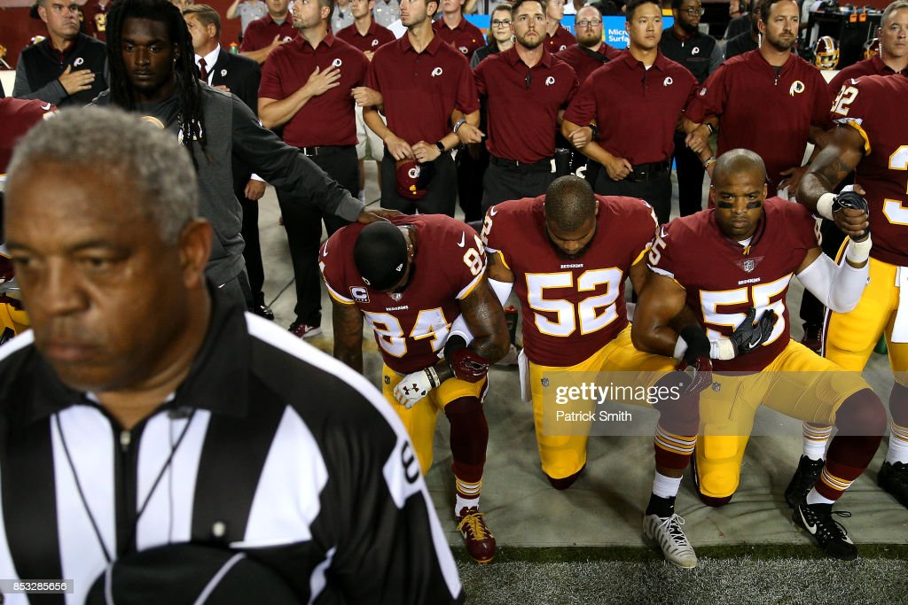 Ryan Anderson #52 of the Washington Redskins locks arms with teammates as they kneel and stand in unison during the national anthem before playing against the Oakland Raiders at FedExField on September 24, 2017 in Landover, Maryland.
