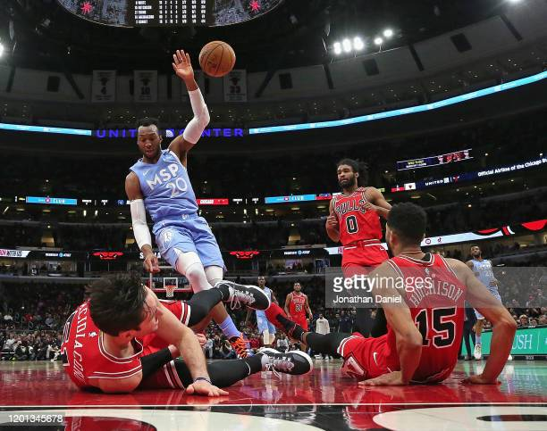 Ryan Arcidiacono and Chandler Hutchison of the Chicago Bulls hit the floor after a collision on an offensive foul by Josh Okogie of the Minnesota...