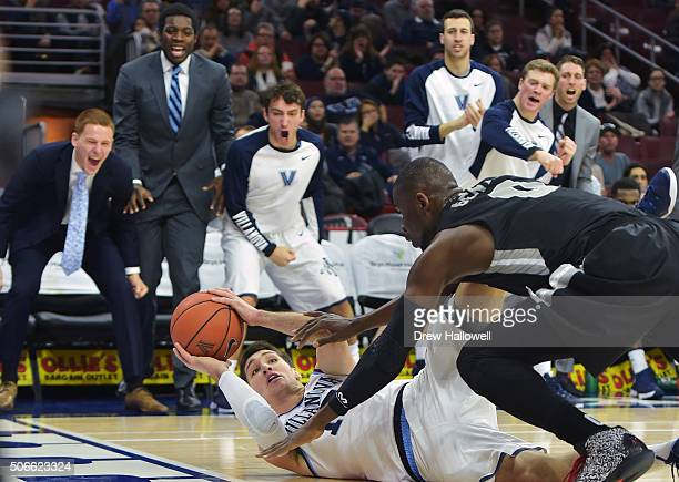 Ryan Arcidiacono of the Villanova Wildcats grabs a loose ball away from Ben Bentil of the Providence Friars as the bench reacts at the Wells Fargo...