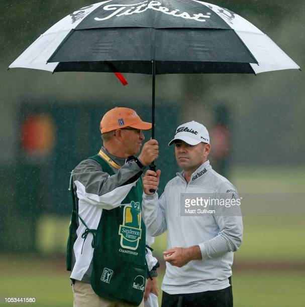 Ryan Armour and his caddie hide from the rain on the sixth hole during the first round of the Sanderson Farms Championship at the Country Club of...