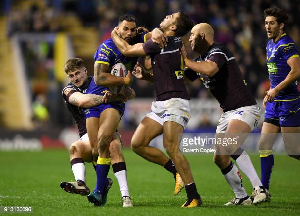 Ryan Atkins of Warrington is tackled by Liam Sutcliffe Matt Parcell and Carl Ablett of Leeds during the Betfred Super League match between Warrington...