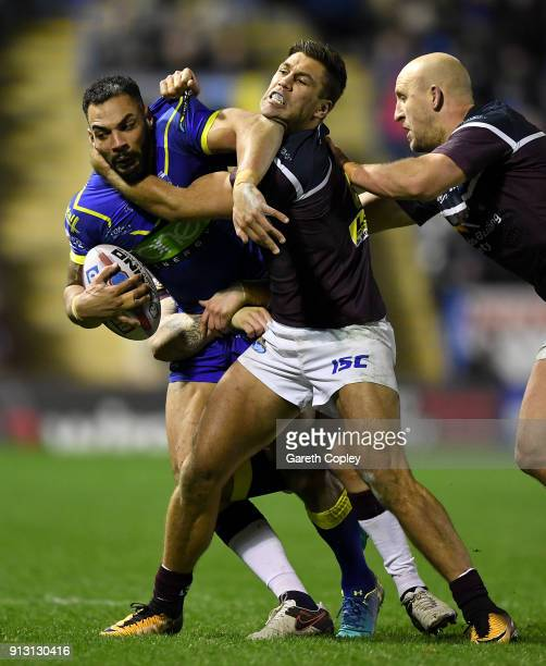 Ryan Atkins of Warrington is tackled by Matt Parcell and Carl Ablett of Leeds during the Betfred Super League match between Warrington Wolves and...