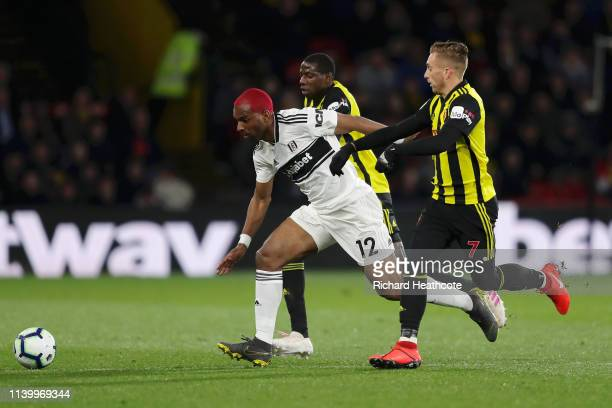 Ryan Babel of Fulham is challenged by Abdoulaye Doucoure of Watford and Gerard Deulofeu of Watford during the Premier League match between Watford FC...