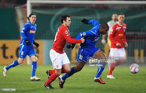 Ryan Babel of Hoffenheim and Marc-Andre Kruska of Cottbus battle for the ball during the DFB Cup quarter final match between Energie Cottbus and 1899...