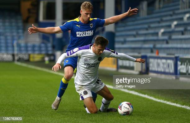 Ryan Barnett of Shrewsbury Town is challenged by Daniel Csoka of AFC Wimbledon during the Sky Bet League One match between AFC Wimbledon and...