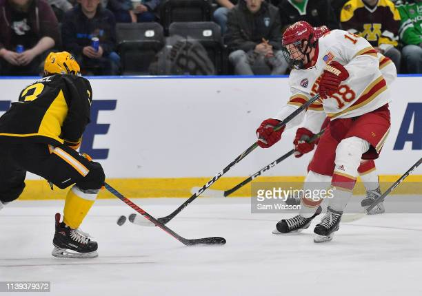 Ryan Barrow of the Denver Pioneers shoots the puck against Patrik Demel of the American International Yellow Jackets during the NCAA Division I Men's...