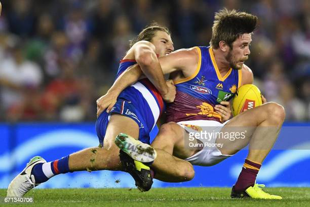 Ryan Bastinac of the Lions is tackled by Marcus Bontempelli of the Bulldogs during the round five AFL match between the Western Bulldogs and the...