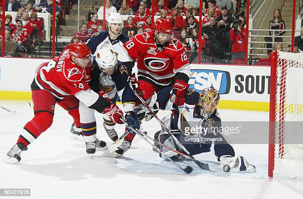 Ryan Bayda and Sergei Samsonov of the Carolina Hurricanes try but are unsuccessful to get the puck past the defense of Johan Hedberg of the Atlanta...