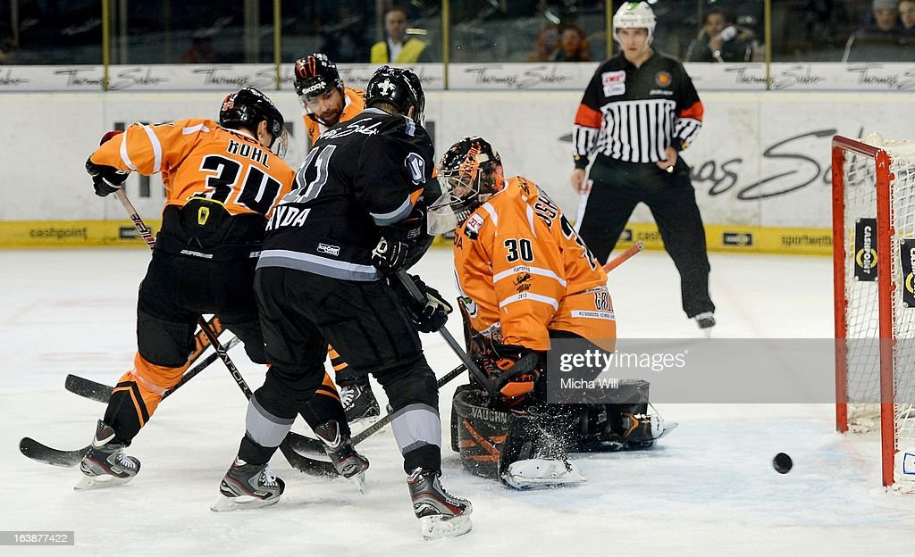 Ryan Bayda (C) of Nuremberg challenges goalie Daniar Dshunussow (R) and Benedikt Kohl (L) of Wolfsburg during game three of the DEL pre-play-offs between Thomas Sabo Ice Tigers and Grizzly Adams Wolfsburg on March 17, 2013 in Nuremberg, Germany.