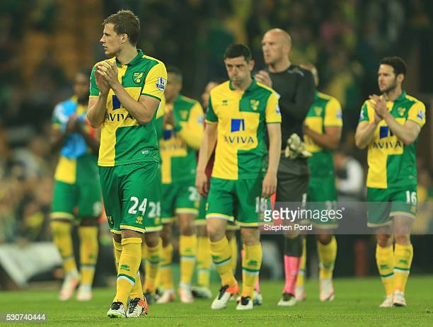 Ryan Bennett of Norwich City looks dejected with team mates after Norwich were relegated during the Barclays Premier League match between Norwich...