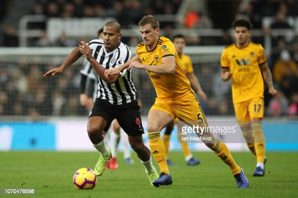 Ryan Bennett of Wolverhampton Wanderers and Salomon Rondon of Newcastle United chase the ball during the Premier League match between Newcastle...