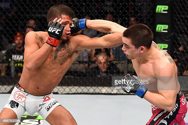Ryan Benoit lands a punch to the face of Sergio Pettis in their flyweight bout during the UFC 185 event at the American Airlines Center on March 14...