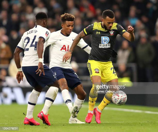 Ryan Bertrand of Southampton holds off Gedson Fernandes and Serge Aurier of Tottenham Hotspur during the FA Cup Fourth Round Replay match between...