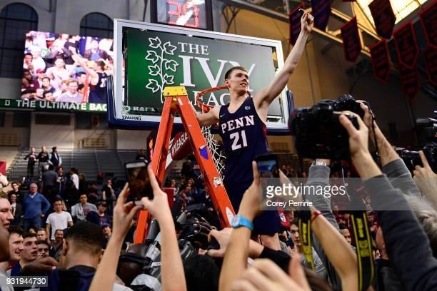 Ryan Betley of the Pennsylvania Quakers holds up a piece of netting after the win at The Palestra on March 11 2018 in Philadelphia Pennsylvania Penn...