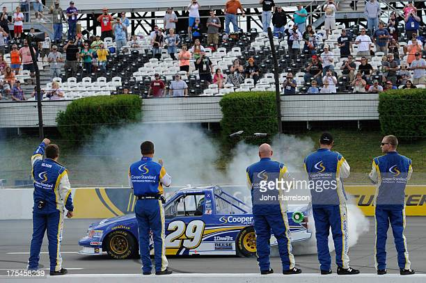 Ryan Blaney driver of the Cooper Standard Ford celebrates with a burnout after winning the NASCAR Camping World Truck Series Pocono Mountains 125 at...