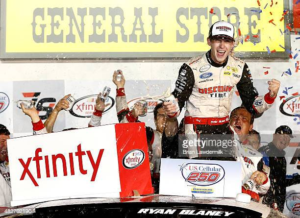 Ryan Blaney driver of the Discount Tire Ford celebrates in victory lane after winning the NASCAR XFINITY Series US Cellular 250 at Iowa Speedway on...