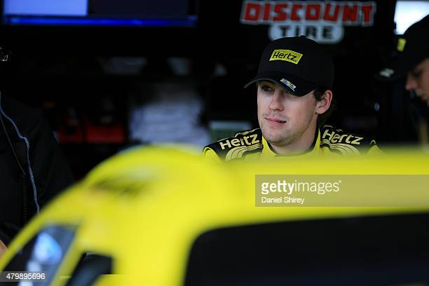 Ryan Blaney driver of the Hertz Ford stands in the garage area during practice for the NASCAR XFINITY Series Buckle Up 200 presented by Click It Or...
