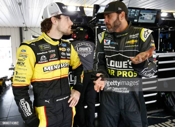 Ryan Blaney driver of the Menards/Duracell Ford talks with Jimmie Johnson driver of the Lowe's for Pros Chevrolet during practice for the Monster...
