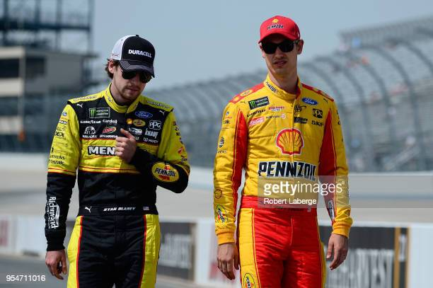 Ryan Blaney driver of the Menards/Duracell Ford talks with Joey Logano driver of the Shell Pennzoil Ford during qualifying for the Monster Energy...