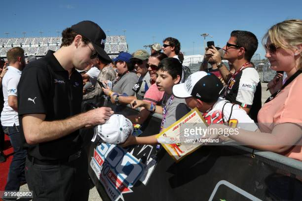 Ryan Blaney driver of the Menards/Peak Ford signs autographs prior to the Monster Energy NASCAR Cup Series 60th Annual Daytona 500 at Daytona...