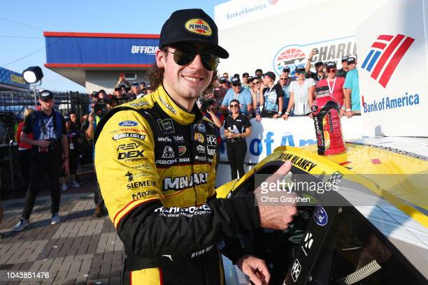 Ryan Blaney driver of the Menards/Pennzoil Ford celebrates in victory lane by placing the Winner's sticker on his car after winning the Monster...
