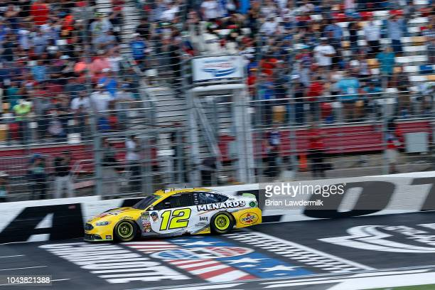 Ryan Blaney driver of the Menards/Pennzoil Ford crosses the finish line to win the Monster Energy NASCAR Cup Series Bank of America Roval 400 at...