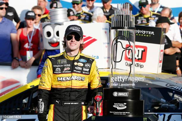 Ryan Blaney driver of the Menards/Pennzoil Ford poses with the trophy in Victory Lane after winning the Monster Energy NASCAR Cup Series Bank of...