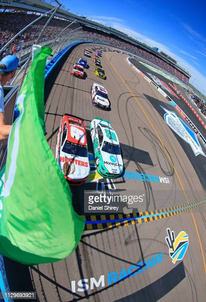 Ryan Blaney, driver of the MoneyLion Ford, and Chase Elliott, driver of the Hooters Chevrolet, take the green flag to start the Monster Energy NASCAR...