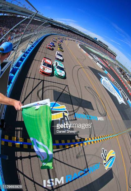 Ryan Blaney driver of the MoneyLion Ford and Chase Elliott driver of the Hooters Chevrolet take the green flag to start the Monster Energy NASCAR Cup...