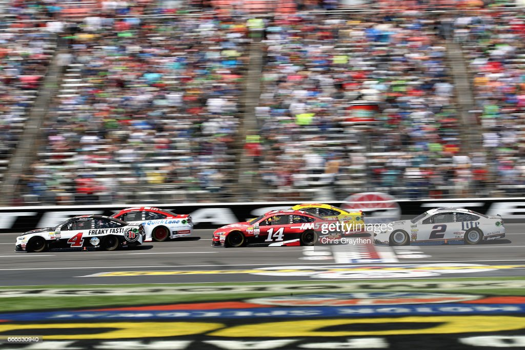 Ryan Blaney, driver of the #21 Motorcraft/Quick Lane Tire & Auto Center Ford, and Kevin Harvick, driver of the #4 Jimmy John's Ford, lead the field past the green flag to start the Monster Energy NASCAR Cup Series O'Reilly Auto Parts 500 at Texas Motor Speedway on April 9, 2017 in Fort Worth, Texas.
