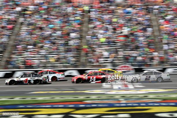 Ryan Blaney driver of the Motorcraft/Quick Lane Tire Auto Center Ford and Kevin Harvick driver of the Jimmy John's Ford lead the field past the green...