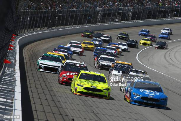 Ryan Blaney driver of the PPG Ford and Paul Menard driver of the Menards/Sylvania Ford lead the field into turn one following the start of the...