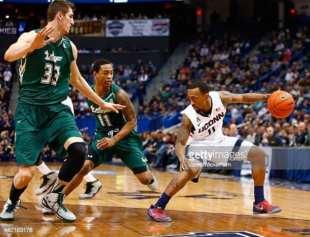 Ryan Boatright of the Connecticut Huskies dribbles in front of defenders Ruben Guerrero and Anthony Collins of the South Florida Bulls in the second...