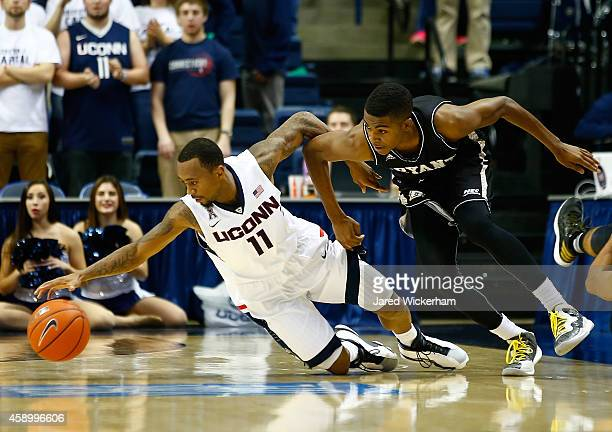 Ryan Boatright of the Connecticut Huskies reaches for the loose ball in front of Hunter Ware of the Byrant Bulldogs in the second half during the...