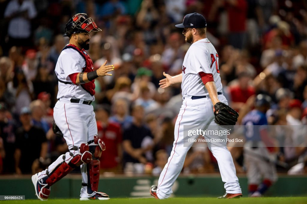 Ryan Brasier #70 of the Boston Red Sox reacts with Sandy Leon #3 after recording the final out during the ninth inning of a game against the Texas Rangers on July 9, 2018 at Fenway Park in Boston, Massachusetts.