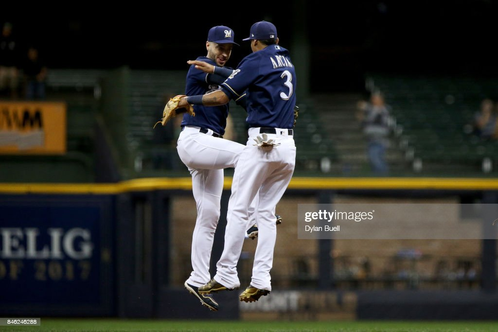 Ryan Braun #8 and Orlando Arcia #3 of the Milwaukee Brewers celebrate after beating the Pittsburgh Pirates 5-2 at Miller Park on September 12, 2017 in Milwaukee, Wisconsin.