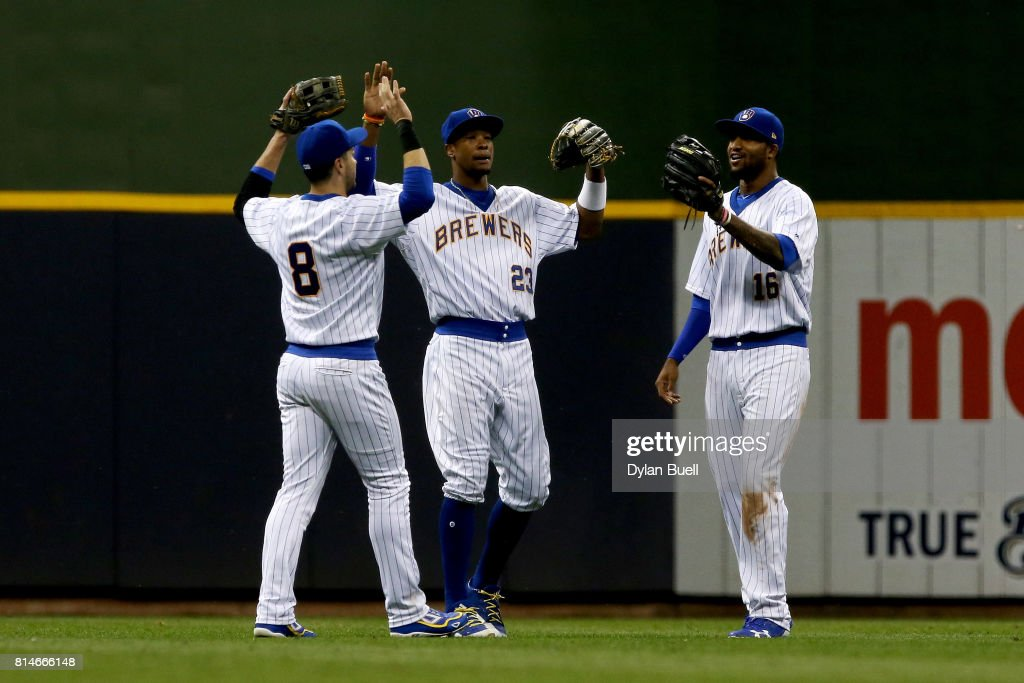 Ryan Braun #8, Keon Broxton #23, and Domingo Santana #16 of the Milwaukee Brewers celebrate after beating the Philadelphia Phillies 9-6 at Miller Park on July 14, 2017 in Milwaukee, Wisconsin.