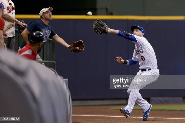 Ryan Braun of the Milwaukee Brewers and a fan reach to catch a fly ball in the seventh inning against the Atlanta Braves at Miller Park on July 6...