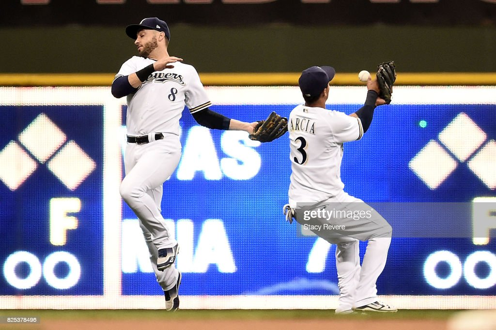Ryan Braun #8 of the Milwaukee Brewers and Orlando Arcia #3 are unable to field a fly ball during the ninth inning of a game against the St. Louis Cardinals at Miller Park on August 1, 2017 in Milwaukee, Wisconsin.