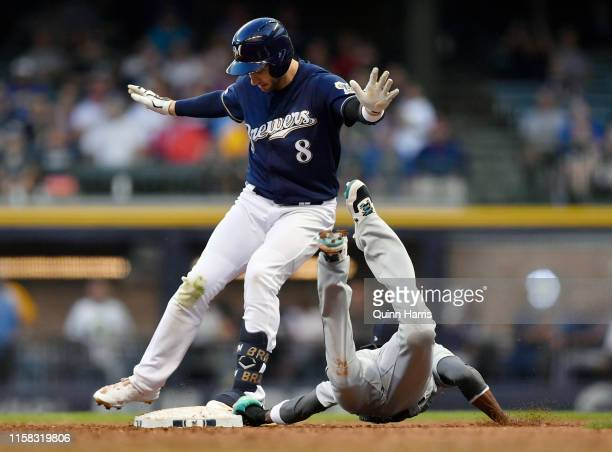 Ryan Braun of the Milwaukee Brewers beats the tag from Dee Gordon of the Seattle Mariners to hit a stand up double in the third inning against the...